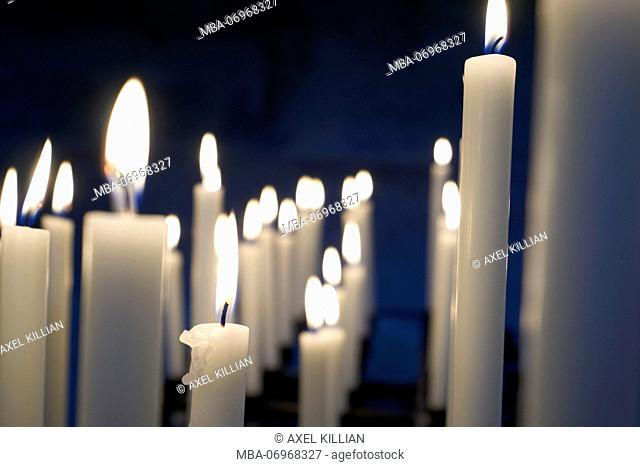 Many white candles are burning in a church, side by side, row, open spacee