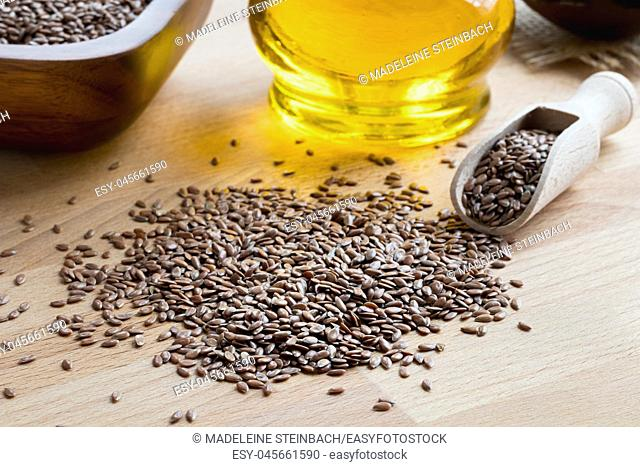 Flax seeds on a wooden table, with flax seed oil in the background