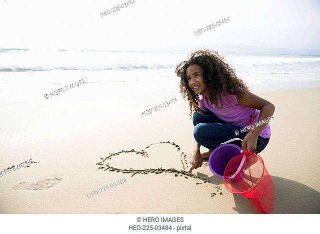 Girl drawing heart-shape in sand on beach