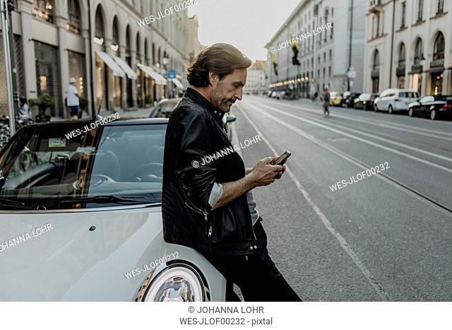 Mature man leaning on car, holding smartphone, Munich, Bavaria, Germany