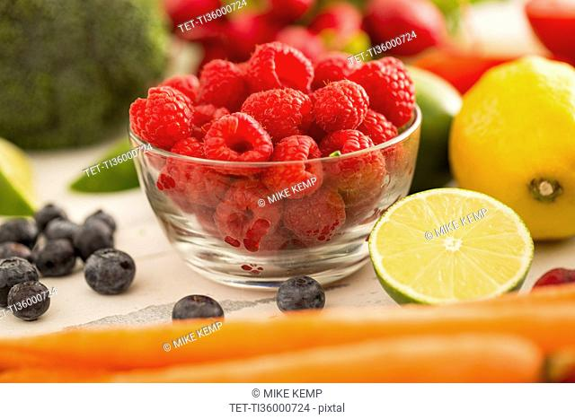 Raspberries in bowl surrounded by fruits and vegetables