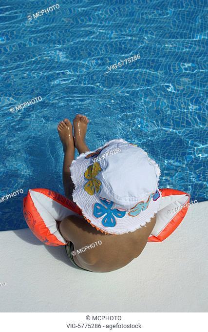Ein kleiner Junge mit Sonnenhut sitzt am Swimming-Pool, Mittelmeer, Spanien| A little boy with a sunhat sitting on the swimming pool - Menorca, Balearen, Spain
