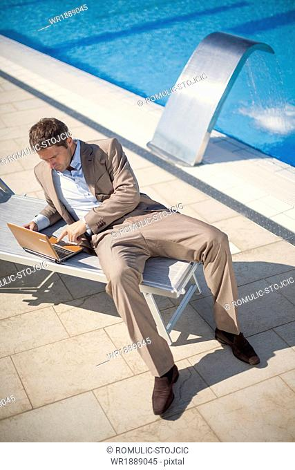 Businessman using laptop on the poolside, Dubrovnik, Croatia