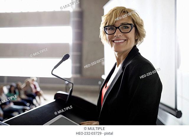 Portrait confident professor at podium in auditorium