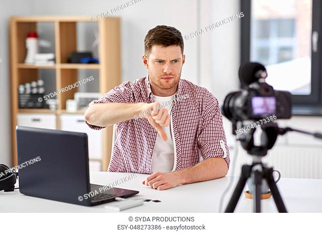 male blogger with camera videoblogging at home