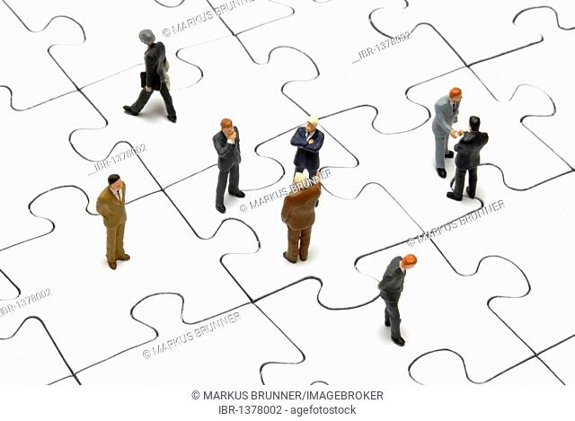 Businessmen figurines on a puzzle, symbolic image for business deals