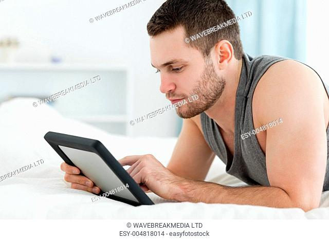 Handsome man using a tablet computer while lying on his belly