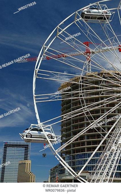 Car ferris wheel with building construction in portrait