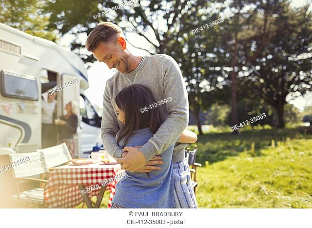 Smiling father hugging daughter outside sunny motor home