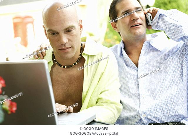 Middle-aged gay couple using technology