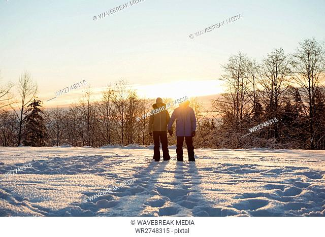 Couple standing on snowy landscape