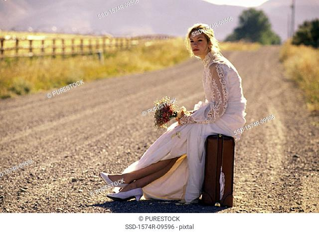 Young bride sitting on a suitcase at the side of a road