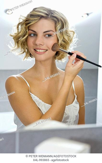 woman putting on make up in bathroom
