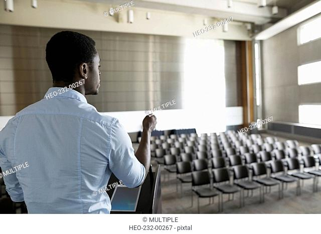 Man rehearsing at podium on stage empty auditorium