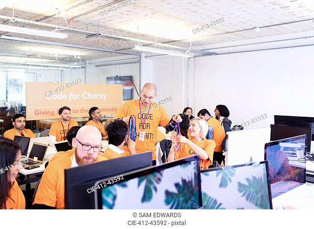 Hackers with lanyards coding for charity at hackathon