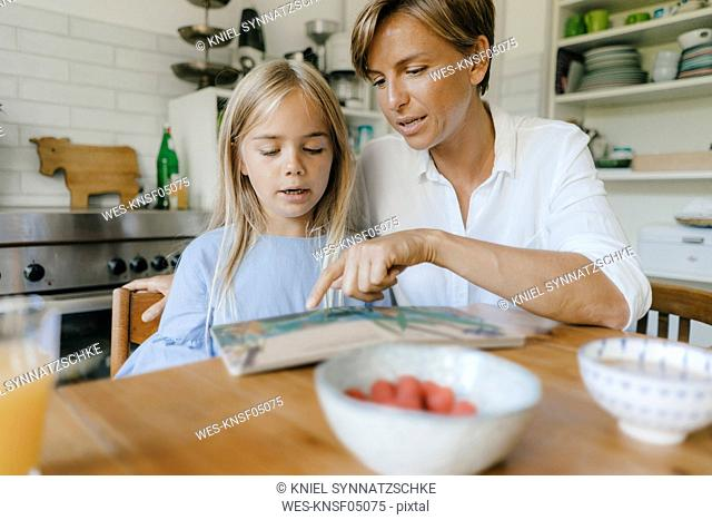 Mother and daughter reading book at table at home together