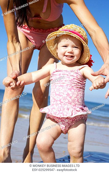 Mother With Young Daughter Walking Along Beach Together
