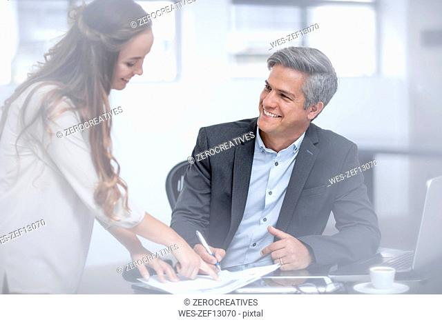 Coworker bringing documents to sign for businessman