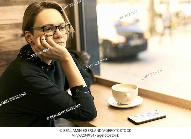 woman sitting at table with coffee cup indoors in café next to window, taking break, in Munich, Germany