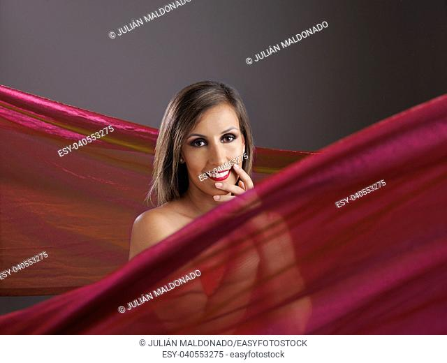 Young woman showing her beauty surrounded by fabrics