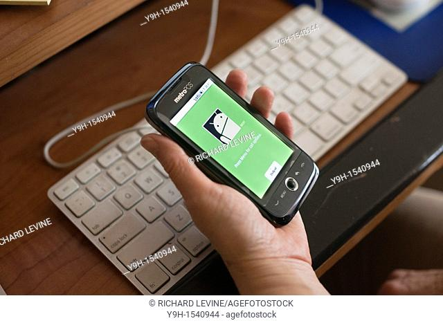 A woman uses her Android operating system powered smart phone. Photo illustration