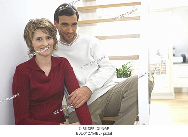 middle aged couple sitting on stairs