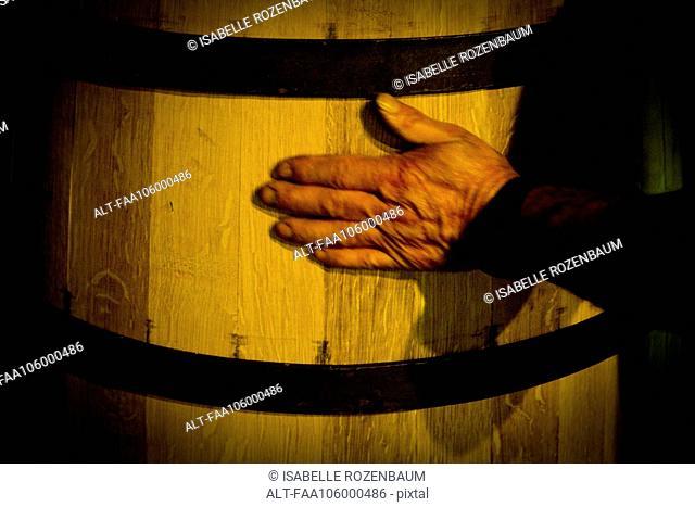 Hand touching wooden cask