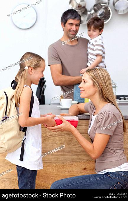 Mother giving her daughter the school lunch
