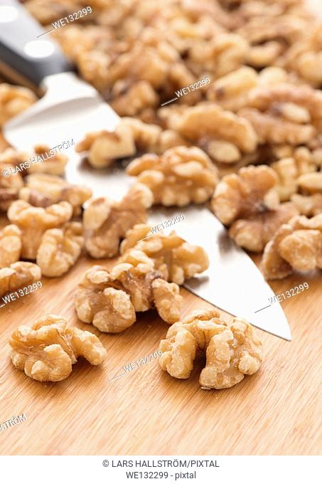 Close up of walnuts and knife on wooden cutting board