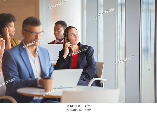 Thoughtful businesswoman looking out window in cafeteria
