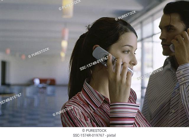Close-up of a businesswoman and a businessman using their mobile phones