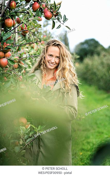 Portrait of smiling woman in apple orchard