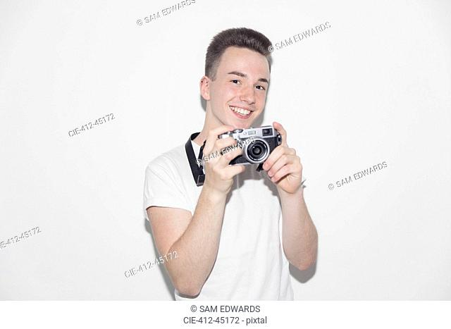 Portrait smiling, confident teenage boy with retro camera