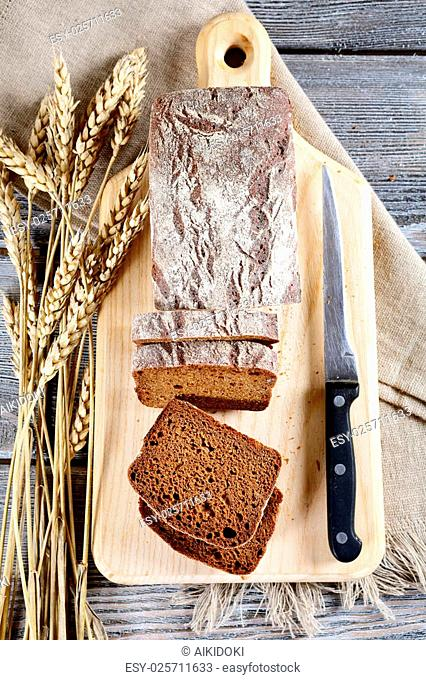 Slices of rye bread, wheat spikelets and knife on a cutting board. Top view
