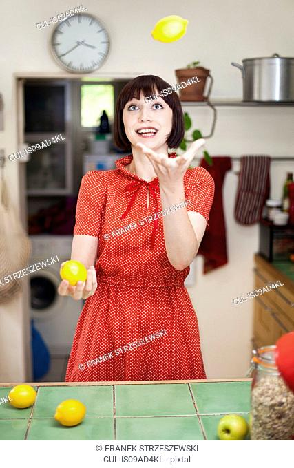 Young woman in kitchen juggling lemons