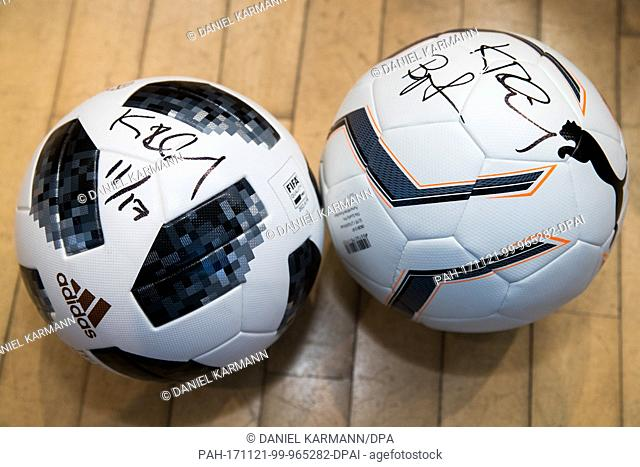 Two footballs of the sportswear manufacturers adidas (L) and Puma lie next to each other prior to a joint panel discussion of the 'Nuremberg News' in Nuremberg
