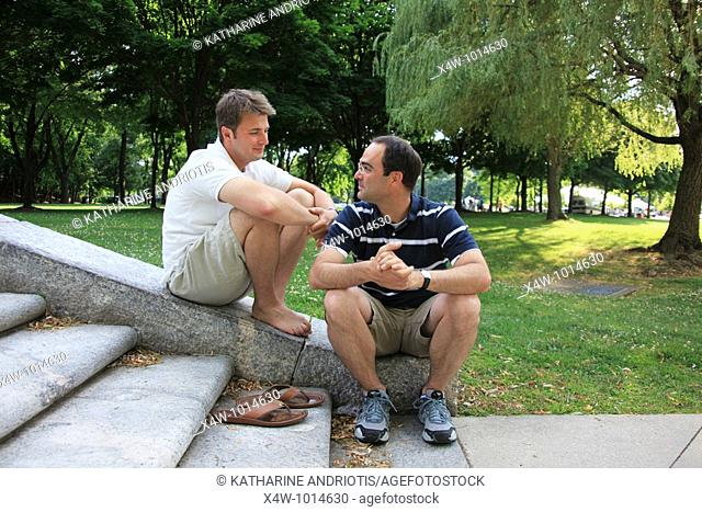 Outdoor portrait of two gay men in a park looking at each other affectionately