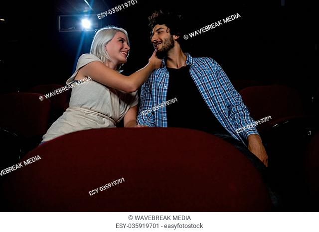 Couple looking at each other while sitting in the theatre