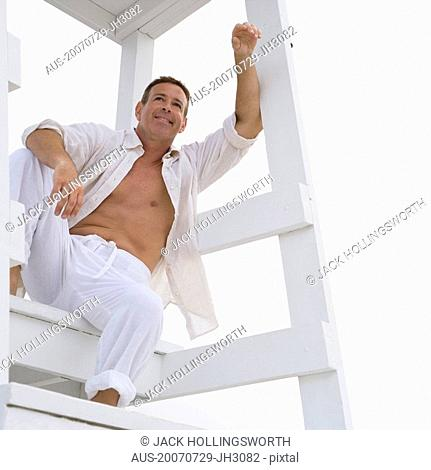 Low angle view of a mature man sitting on a lifeguard hut and smiling
