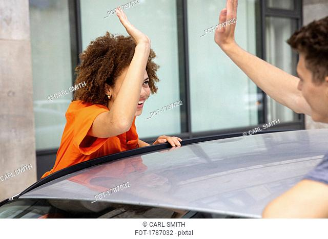 Young couple high-fiving over car