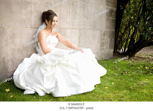 Bride sitting at a wall