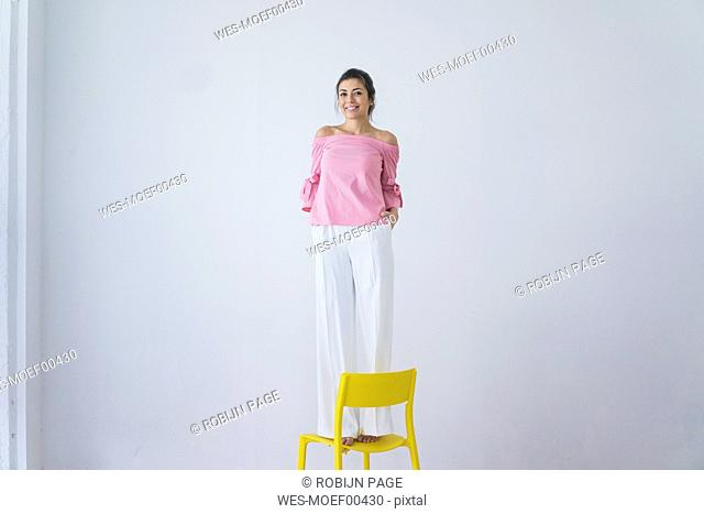 Portrait of laughing woman standing on yellow chair