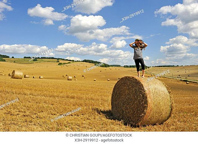 little girl standing up on a straw roll in an harvested field, Allier department, Auvergne-Rhone-Alpes regionFrance, Europe
