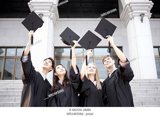 Portrait of smiling college graduates in gowns holding hats looking up