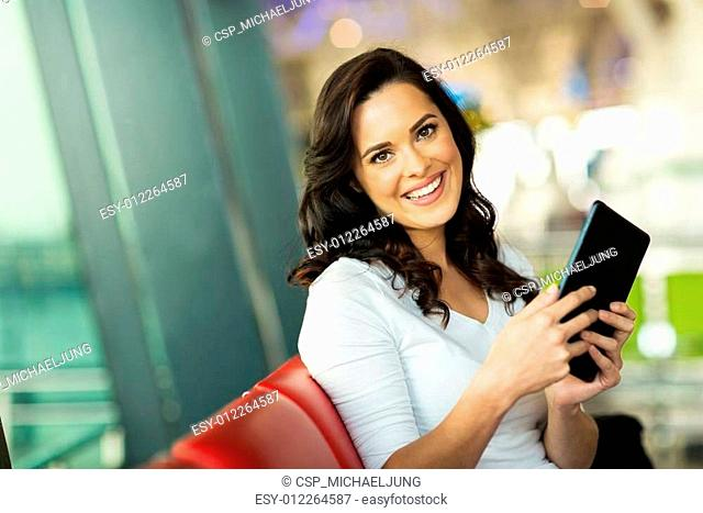 attractive woman holding tablet computer at airport