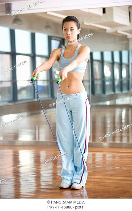 a woman doing exercises with a rope