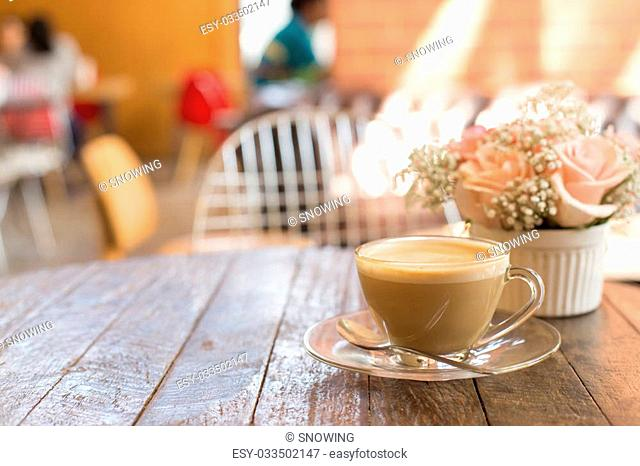 hot coffee and bouquet of flower on grunge wood table