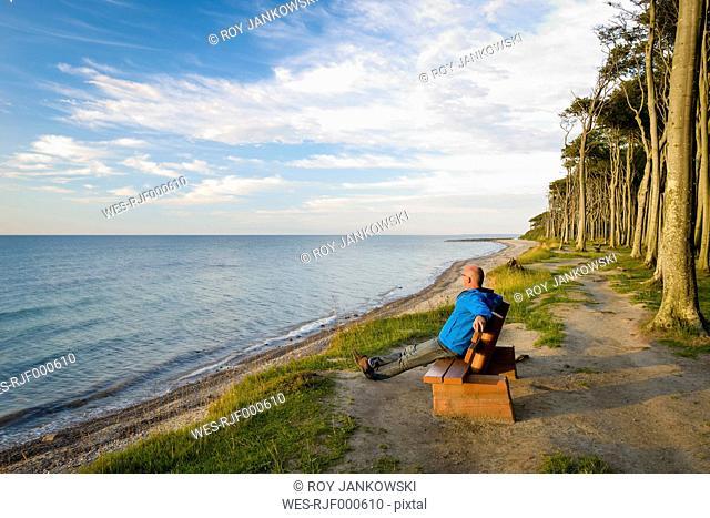 Germany, Nienhagen, Baltic Sea, Gespensterwald, beach, men sitting on bench in the morning