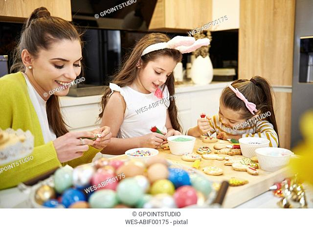 Mother with daughters decorating Easter cookies in kitchen