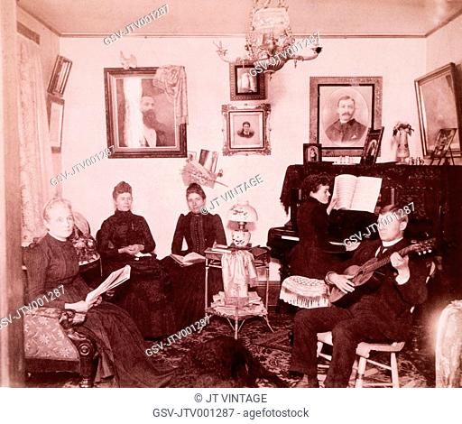 Family Sitting in Parlor While One Plays Piano and One Plays Guitar, USA, Circa 1890